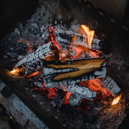 in an old dark barbecue, firewood, ashes, a bonfire. In the dark and gloomy colors.