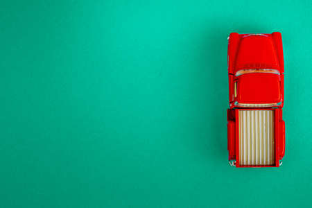 Red Retro car pickup on a blue-green-aquamarine background. Top view with copy space. Flat lay