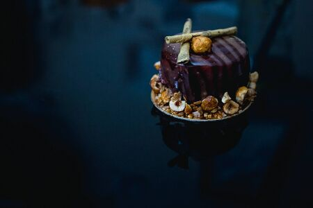 Luxury chocolate cake-cake decorated with a golden decor of caramelized popcorn on a dark background. Flat lay. Close-up. Copy space Stock Photo
