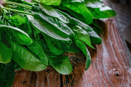 A bunch of young fresh juicy green spinach on a rustic wooden old-time red background. Flat lay. Copy space
