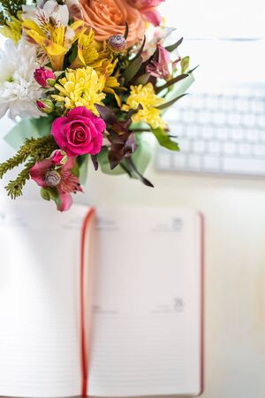 A stylish bouquet with fresh spring flowers is on the desktop near the keyboard and handwritten paper notebook - a diary. Blur, selective focus.