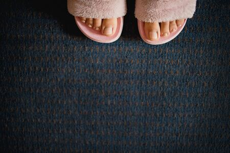 female legs with a pedicure in pink fluffy slippers on a dark blue carpet background. Copy space, flat lay, minimalism.