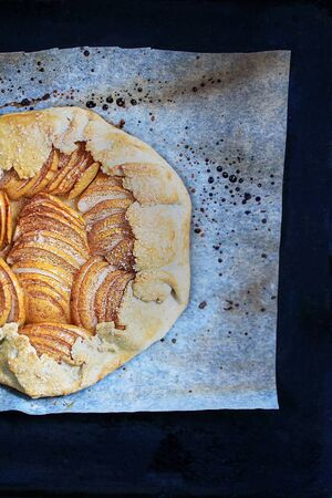 Apple galette - pie on baking parchment and dark background. Copy space, flat lay.