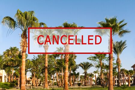 Crisis in the tourism industry due to outbreaks of coronavirus. Stopped traveling, red stamp text. Canceled text on a tropical beach with palm trees. Cancellation of a cruise due to the Covid-19 pandemic. Archivio Fotografico