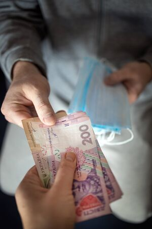 Speculation on medical masks. people illegally sell masks very expensive because they are in short supply. hands pass masks for money, Ukrainian hryvnia. World pandemic coronavirus Covid-19, Pneumonia, medicine