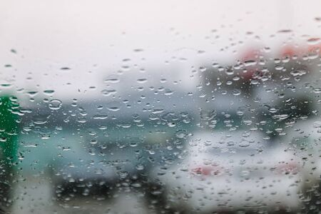 Traffic stands still, on a cold, wet day, shot through a windscreen, focusing on the rain droplets, tailights out of focus. View from car glass window. Conceptual bad weather background