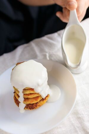 A circumcised man in a black T-shirt holds a white gravy boat in his hands and pours the curd cheesecakes on a plain white tablecloth with sour cream sauce. Concept, simple healthy breakfast