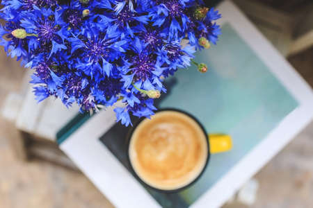 on the balcony there is a white wooden table with a thick book, a yellow cup of coffee and a vase with cornflowers