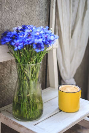 on the balcony is a white wooden table with a yellow cup of coffee and a vase with cornflowers.