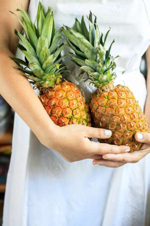 cropped young woman in a white cook apron holds in her hands two ripe and juicy pineapples.