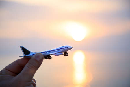 toy plane in hand against the backdrop of a beautiful sea sunset. Silhouette. Copy space