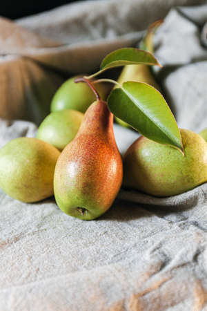 Ripe pears are scattered on a plain linen tablecloth. Simple village life and food. Top view, copy space
