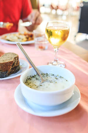 Turkish vegetable white cream soup with spices in a restaurant on the table with a glass of wine, bread. Lunch at the restaurant of the resort hotel Alanya, Turkey 免版税图像