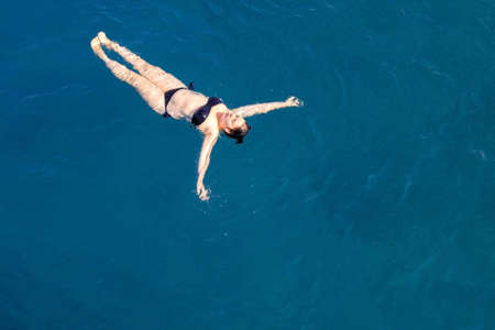 aerial top view happy young woman in black swimsuit swims in the Red Sea, Egypt, Sharm el Sheikh. Vacation and adventure. Blue water. Top view of a lazy girl resting in the sea-ocean. Copy space