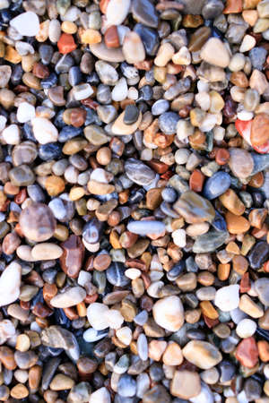 Background of colored sea pebbles on the beach of Alanya, Turkey. Seamless texture