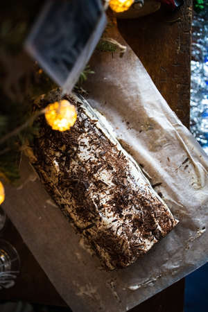 Traditional Christmas chocolate roll with cream on a background of Christmas tree lights on a dark background. View from above 免版税图像