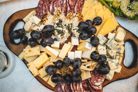 Cheese and meat platter on a wooden board on a festive table. View from above. 免版税图像