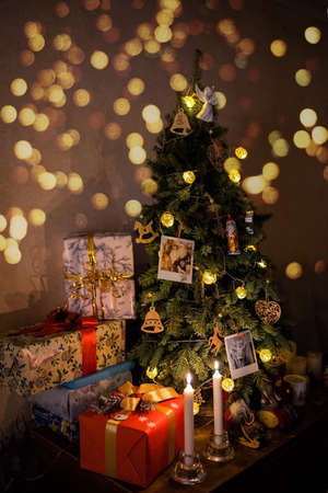 beautiful wrapped boxes with gifts near the Christmas tree, there are candles, lights nearby, family photos and a garland are hanging on the tree 免版税图像