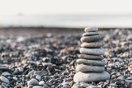 Pyramid of gray pebble stones on the beach of Turkey at sunrise. Zen concept, relaxation. calmness, balance