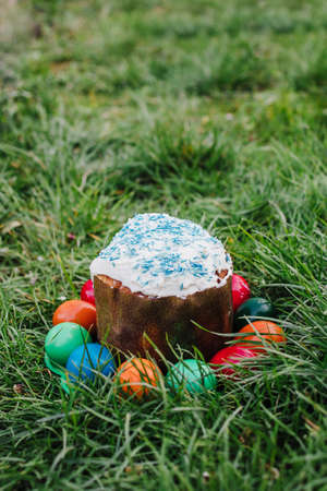 painted and decorative Easter cake and eggs in the grass. Top view, copy space