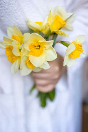 woman in white holds yellow flowers daffodils in her hands