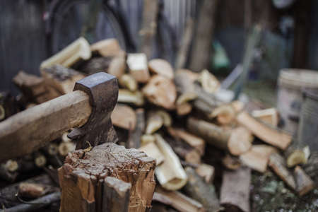 Big ax with chopped woods blurred on background.