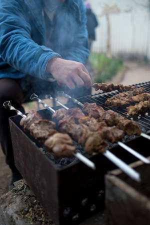A man prepares on the grill delicious barbecue. shish kebabs on skewers