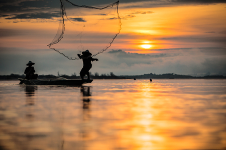 Silhouette fisherman on the boat setting net with sunrise Stock Photo