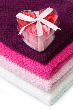 red and pink soap foam roses in a heart-shaped box on bath towels photo