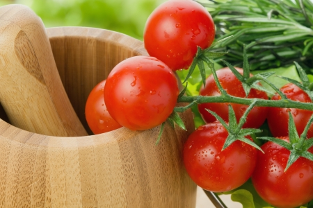 potherb: fresh cherry tomatoes closeup with potherb and pounder Stock Photo