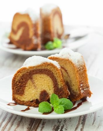 Vanille en chocolade taart gesneden met munt laves op houten tafel