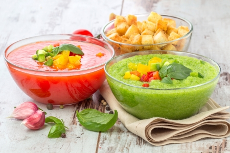 Delicious cold red and green gazpacho soup with garlic croutons in  bowls photo