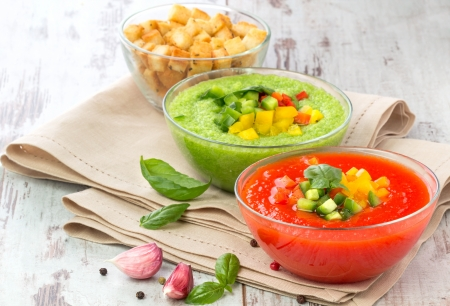 Delicious cold red and green gazpacho soup with garlic croutons in  bowls
