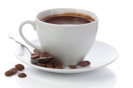 Warme chocolademelk in witte kop en chocolade chips op wit wordt geïsoleerd