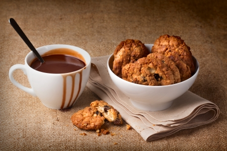 Hot chocolate in white cup and oatmeal cookies in a bowl photo