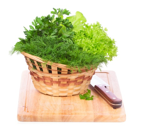 Green herbs in a basket on chopping board isolated on white background photo