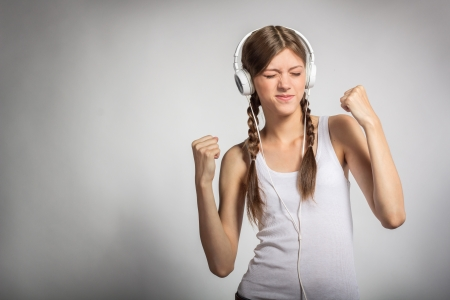 eye's closed: Young woman with headphones listening music and dancing with her eyes closed