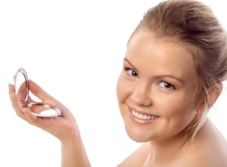 ojos marrones: Retrato de una hermosa mujer joven con ojos marrones sosteniendo un espejo. La piel clara.