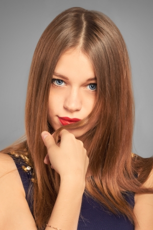portrait of friendly smiling teenage girl looking to the camera  holding lock of hair  studio shot