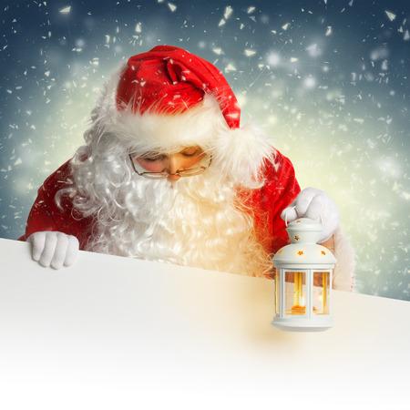 Santa Claus looking down on white blank banner holding a shining lantern