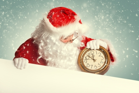 Weihnachtsmann mit leere weiße Fahne, die eine Uhr, die mehrere Minuten vor Mitternacht Standard-Bild - 24516183