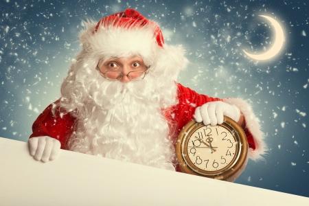 Weihnachtsmann mit leere weiße Fahne, die eine Uhr, die mehrere Minuten vor Mitternacht Standard-Bild - 24516184