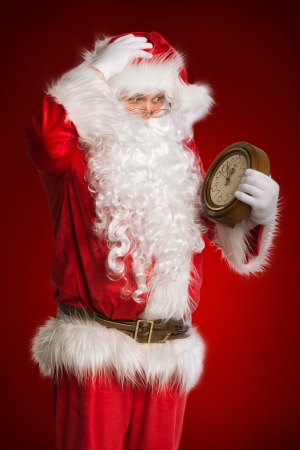 Santa Claus holding a clock showing several  minutes to midnight photo