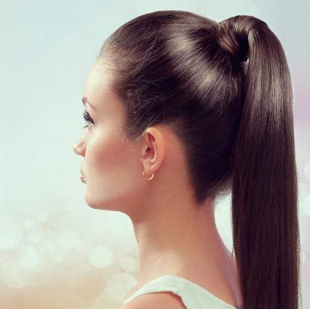 Jonge vrouw met een gezonde glanzende bruine haren gezet in paardenstaart.
