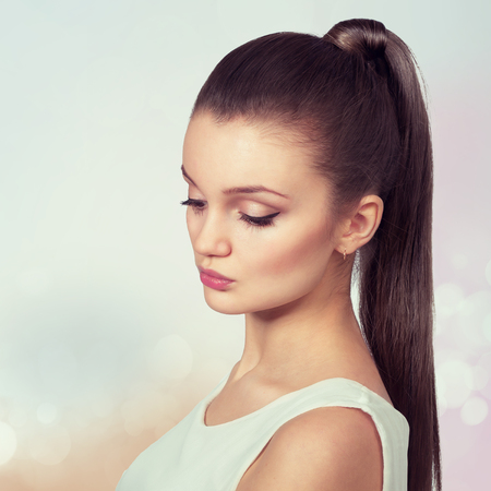 pony tail: Young female with healthy shining brown hairs put in pony tail.