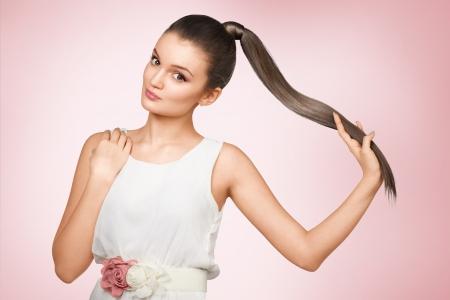 cola mujer: Femail joven con el sano brillante pelo marrón poner en cola de caballo.