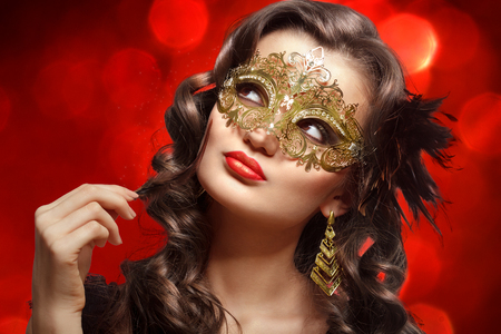 Young beautiful woman in golden carnival mask. photo