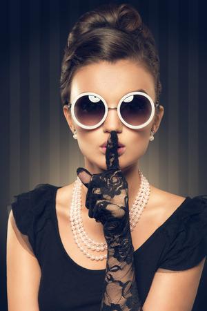 shh: portrait of beautiful brunette woman wearing pearl  jewelry and sunglasses  retro style