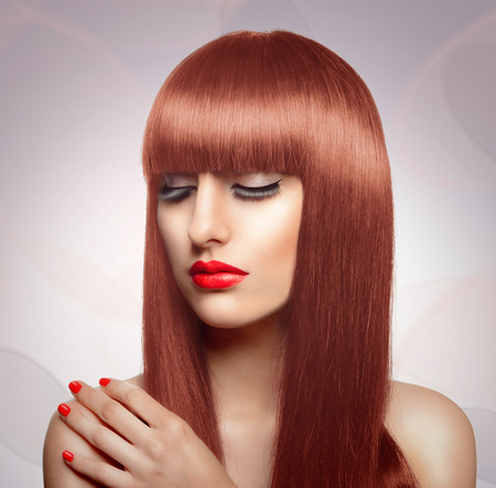 Portrait of beautiful fashion woman with long healthy red hair and fringe hairstyle