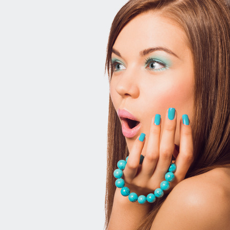 Young surprised woman holding a turquoise bracelet with bright manicure.